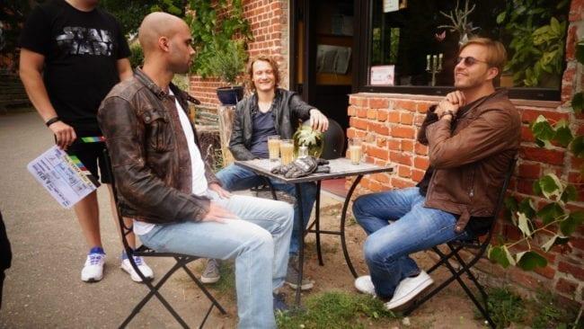 Die Darsteller sitzen an einem Bistrotisch und haben Spaß